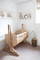 A wooden cradle in this child's bedroom adds to the rustic, earthy nature of the room.  His name, Luca, is written in rope above the cot