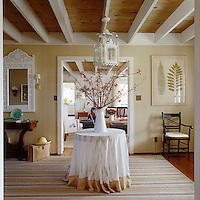 An antique lantern hangs from a beamed ceiling above a wild flower arrangement and round, cloth covered table
