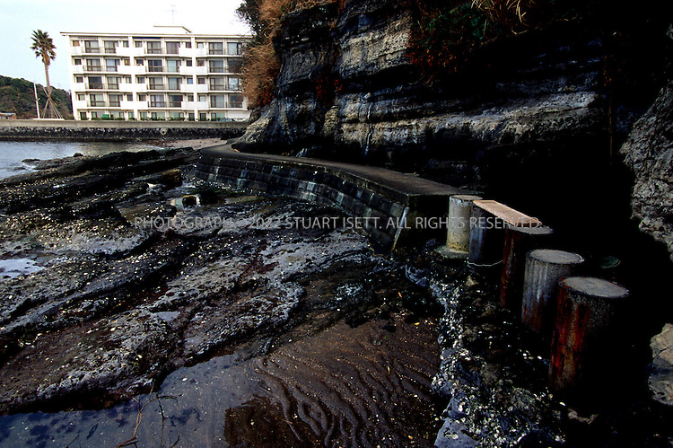 3/14/01--Kanagawa, Japan..The beach and cave (right) where the British Hostess Lucie Blackman was murdered in 2000. Behind are the condominiums where her accussed killer, Jojo Obara, lived...All photographs ©2003 Stuart Isett.All rights reserved.This image may not be reproduced without expressed written permission from Stuart Isett.