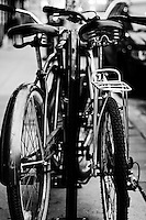 Two Bicycles chained side by side to a bike rack.