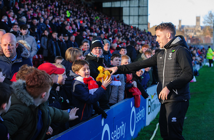 Lincoln City's Shay McCartan gives away a Kick It Out t-shirt to a young fan at half time<br /> <br /> Photographer Chris Vaughan/CameraSport<br /> <br /> The EFL Sky Bet League Two - Lincoln City v Northampton Town - Saturday 9th February 2019 - Sincil Bank - Lincoln<br /> <br /> World Copyright © 2019 CameraSport. All rights reserved. 43 Linden Ave. Countesthorpe. Leicester. England. LE8 5PG - Tel: +44 (0) 116 277 4147 - admin@camerasport.com - www.camerasport.com