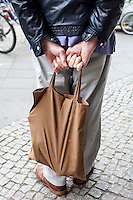 Berlino, quartiere Kreuzberg. Un uomo attende davanti a un supermercato tenendo una borsa con due mani dietro alla schiena --- Berlin, Kreuzberg district. A man waiting outside of a supermarket holding with both hands a bag behind his back
