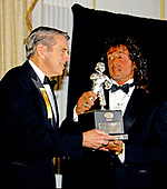 American actor, director, screenwriter, and producer Sylvester Stallone, right, accepts the President's Council on Physical Fitness award from former Washington Redskins head coach George Allen, left, at the Washington, DC Touchdown Club dinner in Washington, DC on January 23, 1988.  .<br /> Credit: Arnie Sachs / CNP