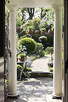A view from the front door of the house through the columned porch to the garden beyond