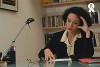 Businesswoman sitting at desk resting head on hand (Licence this image exclusively with Getty: http://www.gettyimages.com/detail/200336692-001 )