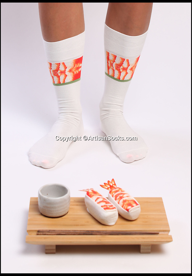 BNPS.co.uk (01202 558833)<br /> Pic: ArtisanSocks/BNPS<br /> <br /> ***Must Use Full Byline***<br /> <br /> Shrimp Ebi sushi socks. <br /> <br /> Soft Sushi Shuffle...<br /> <br /> Now, should you wish to, you can make your sock draw look like a sushi bar.<br /> <br /> These morsels of mouthwatering sushi might look tantalising but you wouldn't want to eat them - because they're actually rolled up socks.<br /> <br /> The super-realistic items of clothing are the latest bizarre trend sweeping the fashion world and have been an instant hit with shoppers.<br /> <br /> Unrolled they look like any other sock but rolled up they form seven different varieties of the raw fish snack, transforming your underwear drawer into a smorgasbord of sushi.<br /> <br /> The life-like 'flavours' include egg (tamago), salmon roe (ikura), shrimp (ebi), octopus (tako), tuna (maguro ), salmon (sa-mon) and trout (masuzishi).<br /> <br /> Sushi socks cost $6 a pair - around £3.70 - and can be bought from artisansocks.com.