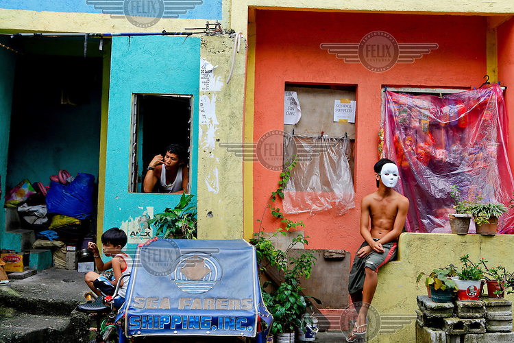 A man sits in the window of a shop-house. Outside a young man sits on a wall wearing a white mask and a small boy squats on a wall next to a cycle rickshaw.