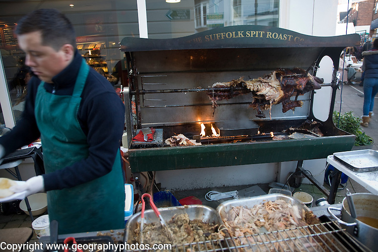 Young man serving food at a hog roast street stall, Woodbridge, Suffolk, England