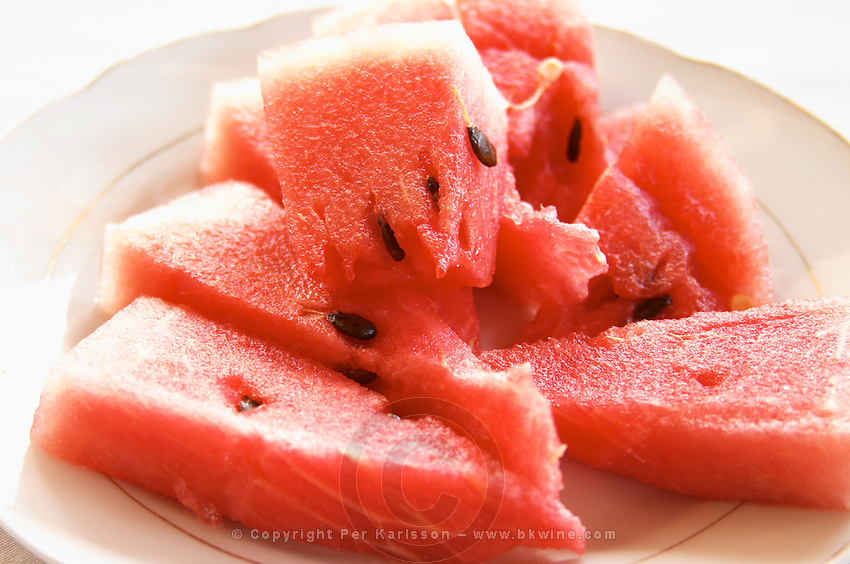 Triangular pieces of red water melon Shalqi on a white plate. Berat lower town. Albania, Balkan, Europe.