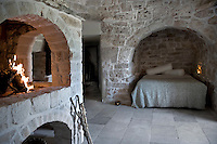 An open fire and niche lighting bring warmth to this bedroom and bed alcove with exposed stone walls