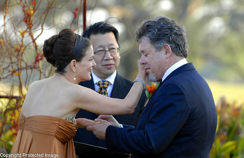 Bernadette Murray wipes tears from Randy Fertel's eye as he places the wedding ring on her finger during an outdoor ceremony in Audubon Park, New Orleans, Saturday, March 10, 2007..(Cheryl Gerber for New York Times).. Weddings, New Orleans Photographer