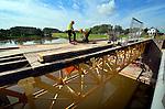 LEERDAM - Langs het spoor bij Leerdam zijn medewerker van Heijmans Restauratiewerken bezig met de afbouw van de historische kraanburg. De brug, waarvan er maar twee zijn in Nederland gaf destijds toegang tot het uit 1815 daterende fort Werk en was uitgevoerd met een opmerkelijk systeem van wegdraaiende rails. In opdracht van Staatsbosbeheer is niet alleen het staal gestraald en van nieuwe okergele verf voorzien, maar is ook het metselwerk, de voegen en het hardsteen vervangen. In september moet de brug weer feestelijk worden geopend.COPYRIGHT TON BORSBOOM