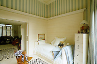 Fresh wooden panelling and blue-and-white striped wallpaper have resulted in this bright and cheerful child's room