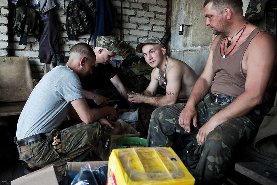 UKRAINE: Frontline of Kamyanka. Ukrainian soldiers peeling some potatoes for the dinner of their unit. <br /> <br /> UKRAINE: Frontline de Kamyanka. Des oldats ukrainiens &eacute;pluchent des pommes de terre pour le d&icirc;ner de leur unit&eacute;.