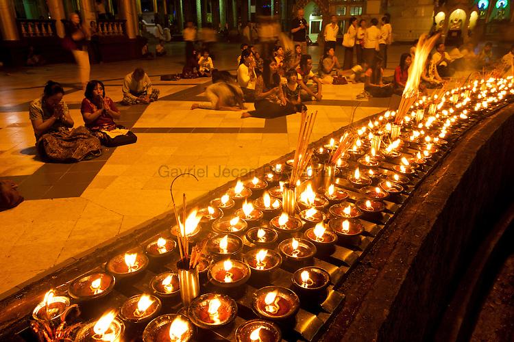 Buddhist fallowers praying at Shwedagon pagoda at night