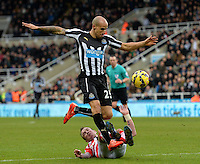 Gabriel Obertan of Newcastle United jumps over a challenge from Glenn Whelan of Stoke City