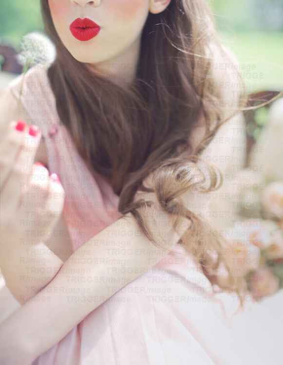 Cropped photo of a beautiful young brunette woman with very long hair in a pastel pink dress, blowing out a dandelion and making a wish, somewhere in nature