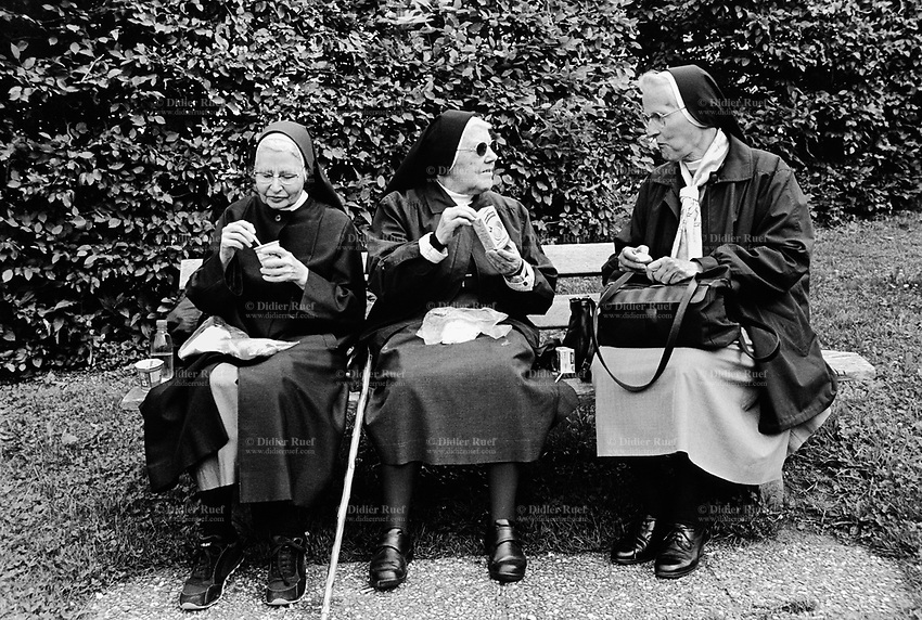 Switzerland. Canton Schwyz. Einsiedeln. Three nuns, seated on a bench outside Einsiedeln Abbey, eat a yoghurt, an apple and an orange juice. for lunch. Einsiedeln Abbey is a Benedictine monastery in the town of Einsiedeln. The abbey is dedicated to Our Lady of the Hermits, the title being derived from the circumstances of its foundation, for the first inhabitant of the region was Saint Meinrad, a hermit. It is a territorial abbey and, therefore, not part of a diocese, subject to a bishop. It has been a major resting point on the Way of St. James for centuries. 31.08.13 © 2013 Didier Ruef