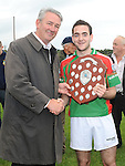 Chairperson of the Louth County Board Padraic O'Connor presents Glen Emmets captain Aidan Monaghan with the Kevin Mullen shield after they beat Naomh Fionnbarra at Monasterboice. Photo: www.colinbellphotos.com