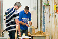 Instructor (blue top) working with a student on a short bricklaying course before building his own garage at home.  Able Skills in Dartford, Kent, runs courses in construction industry skills like, bricklaying, carpentry and tiling.