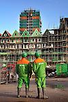ZAANDAM - In Zaanstad lijken de kleuren van de woningen van project Rustenburg aangepast te zijn aan de bedrijfskleding van bouwer Bam Woningbouw. Het door architecten Mattijs Rijnboutt en Kees Rijnboutt ontworpen complex waarin een drie verdiepingen diepe parkeergarage, ruim honderd woningen, een bioscoop met zes zalen en 11.000 m2 winkelruimten zijn ondergebracht, is echter grotendeels uitgevoerd in de traditionele groene streekkleuren, met ouderwetse oranje dakpannen. De monderne woningen onder de zeventien etage hoge woontoren, zijn daarnaast vormgegeven als grachtenhuizen, Zaanse pakhuizen en zaagtandwoningen. COPYRIGHT TON BORSBOOM
