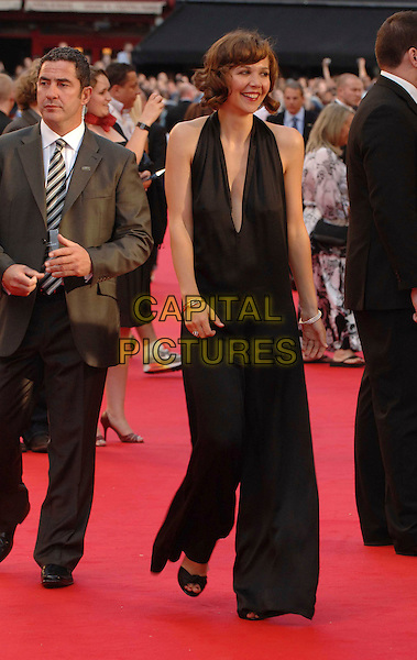 """MAGGIE GYLLENHAAL .Attending the UK Premiere for the new Batman movie """"The Dark Knight"""", Odeon Leicester Square, London, England,.July 21st 2008..full length black catsuit pantsuit halterneck low cut plunging neckline walking open toe shoes bracelets .CAP/WIZ.©Wizard/Capital Pictures"""