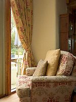 A large and comfortable armchair in the living room faces onto the garden and is piled with scatter cushions