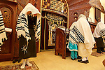 Israel, Bnei Brak. The Synagogue of the Premishlan congregation on Purim holiday. The Rabbi is leading the Priestly Blessing prayer, his son under his Talith to prevent him from looking at the heads or hands of the Priests, 2005<br />