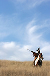 A Native American Indian man on horseback scouting for enemies or hunting for food in the prairie of South Dakota