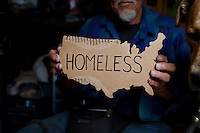 """Ventura, California, July 21, 2010 - A portrait of Gary Seymour holding a cardboard map of the United States in his camper. Mr. Seymour has been homeless off and on for the last thirty years. He currently lives in a camper parked left to him by his father that is parked in the driveway of a friend's mother. Because it is an illegal camp, Mr. Seymour is considered homeless. He says, """"I work odd jobs, landscaping and whatnot to make a little money. I am trying to get back on my feet."""" Mr. Seymour is proud that he does not panhandle. """"I earn my own living without asking people for handouts."""" ..."""