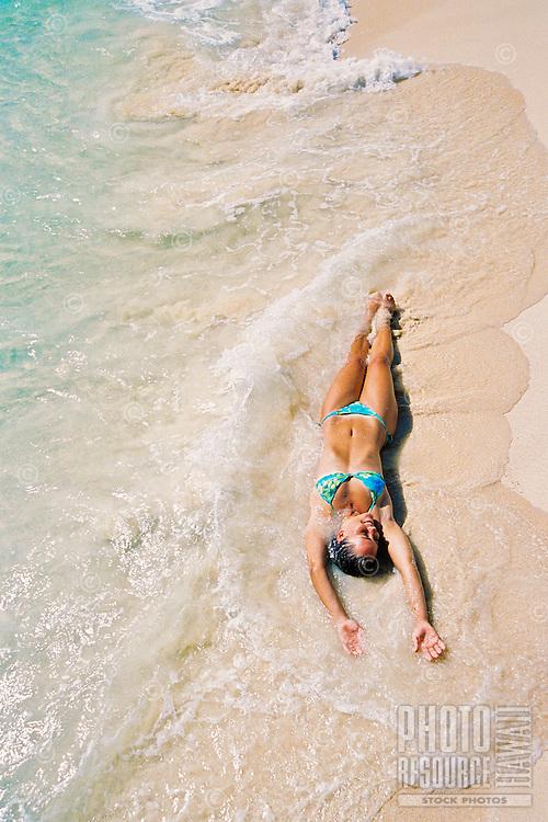 Young woman enjoying the sun at the beachside