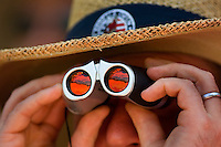 A fan uses binoculars to watch golfers play during the 2007 Wachovia Championships at Quail Hollow Country Club in Charlotte, NC.