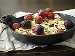 Baked cheese with roasted grapes and fresh herbs