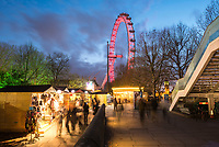 Christmas Market in Jubilee Gardens, with The London Eye at night, South Bank, London, England