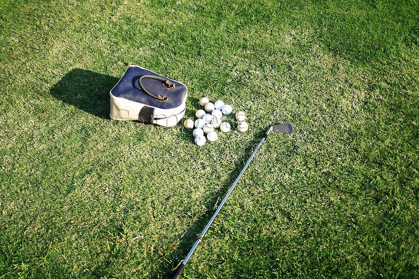 golf club lies next to bag of old practise balls at driving range