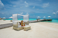 Maldives, Rangali Island. Conrad Hilton Resort. Woman sitting in canopy chair on the beach. (MR)