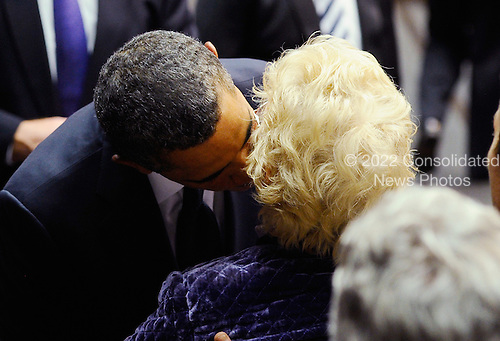 """United States President Barack Obama (L) hugs Mary Stoddard, wife of Tucson shooting victim Dorwin Stoddard, who died after he was shot in the head, at the event """"Together We Thrive: Tucson and America"""" honoring the January 8 shooting victims at McKale Memorial Center on the University of Arizona campus on Wednesday, January 12, 2011 in Tucson, Arizona. The memorial service is in honor of victims of the mass shooting at a Safeway grocery store that killed six and injured at least 13 others, including U.S. Representative Gabrielle Giffords (Democrat of Arizona), who remains in critical condition after being shot in the head. Among those killed were U.S. District Judge John Roll, 63; Giffords' director of community outreach, Gabe Zimmerman, 30; and 9-year-old Christina Taylor Green. .Credit: Kevork Djansezian / Pool via CNP"""