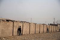 Men urinate against a wall at the Kashgar Sunday Animal Market in Kashgar, Xinjiang, China.