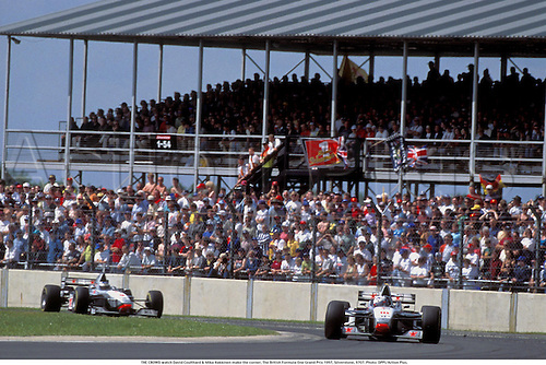 THE CROWD watch David Coulthard & Mika Hakkinen make the corner, The British Formula One Grand Prix 1997, Silverstone, 9707. Photo:  Action Plus....formula one f1.motor sport.motorsport.motorsports.grand prix gp.racing car cars.crowds spectator spectators supporters fans