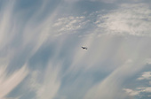 Jet aircraft passing below cirrus clouds driven by high winds above southern England.