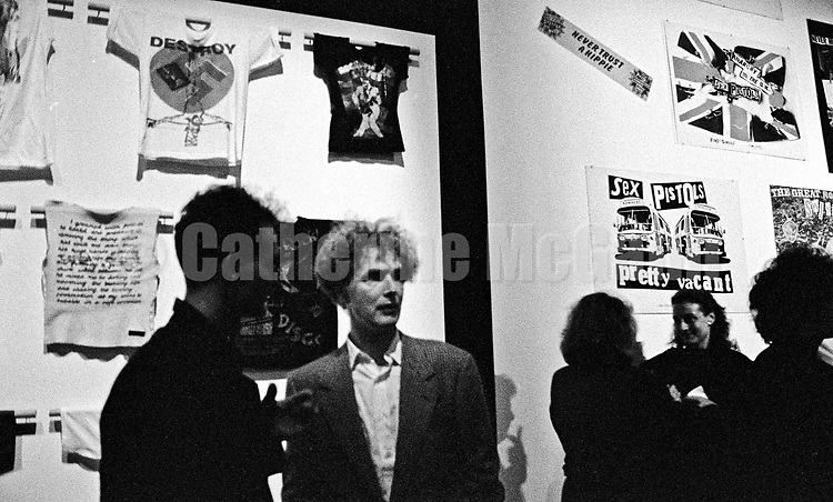 "September 14, 1988:  Malcolm McLaren (1946 2010) center, in front of an installation of Sex Pistols ephemera, including t-shirts he designed with Vivienne Westwood, at the opening reception of his exhibition at the New Museum of Contemporary Art in New York City, titled ""Impresario: Malcolm McLaren and the British New Wave""."