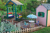 Children's play area with small tables, coverd sitting structure, and playhouse
