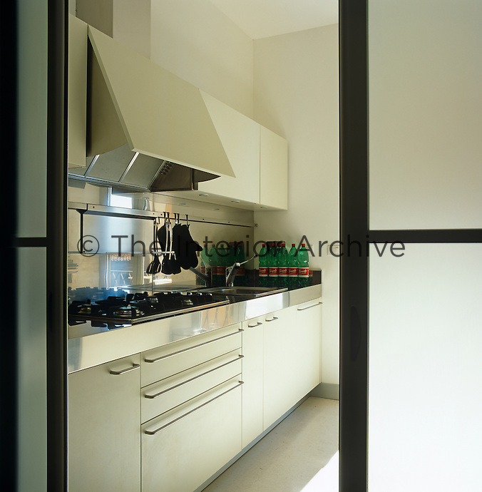 The contemporary kitchen is glimpsed through an open sliding door with opaque glass panels