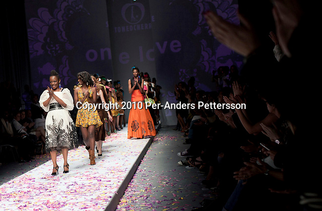 CAPE TOWN, SOUTH AFRICA - AUGUST 13: Nkhensani Nkosi (l) greets the crowd after her show with Stoned Cherrie, her fashion label, at the African Fashion International Cape Town fashion week on August 13, 2010, at the Cape Town International Convention Center, in Cape Town, South Africa. Stoned Cherrie is founded by Nkhensani Nkosi, age 37, a mother of four and a celebrated fashion designer, entrepreneur, television personality and an actress in South Africa. She launched her new collection Love Movement at this event. (Photo by Per-Anders Pettersson)