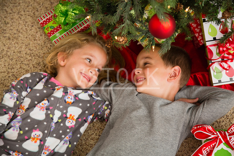 Brother (6-7) and sister (6-7) lying by Christmas tree