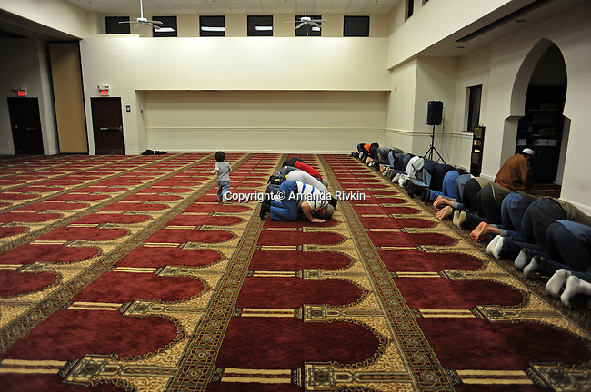 Muslim men are seen during Friday evening prayers being led by Sheikh Osama Bahloul, an Egyptian immigrant, as his son Adam, 2, runs around in the prayer room at the Islamic Center in Murfreesboro, Tennessee on January 4, 2012.