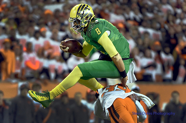 CORVALLIS, OR - NOVEMBER 29:  Quarterback Marcus Mariota #8 of the Oregon Ducks hurdles safety Justin Strong #39 of the Oregon State Beavers during the first quarter of the game at Reser Stadium on November 29, 2014 in Corvallis, Oregon.  (Photo by Steve Dykes/Getty Images) *** Local Caption *** Marcus Mariota;Justin Strong