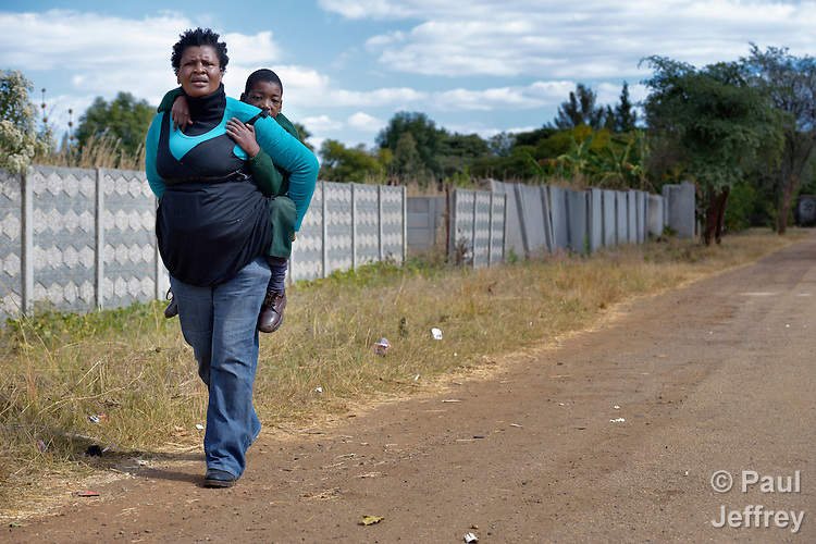 Tarisayi Zhanje carries her grandson, Hailey Kushaya, home from school in Harare, Zimbabwe. She cares for the 9 year old since his parents died. At school he uses an appropriately-designed and fitted wheelchair provided by the Jairos Jiri Association with support from CBM-US.