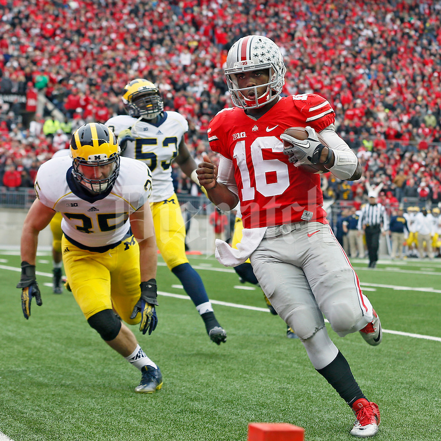Ohio State Buckeyes quarterback J.T. Barrett (16) turns the corner and scores on a rushing touchdown against Michigan Wolverines linebacker Joe Bolden (35) in the 3rd quarter of their game at Ohio Stadium in Columbus, Ohio on November 29, 2014.  (Dispatch photo by Kyle Robertson)