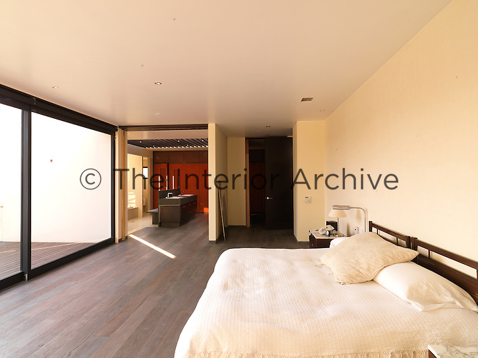 The sparsely furnished master bedroom benefits from an ensuite bathroom